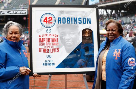 Rachel Robinson, left, widow of Jackie Robinson, and daughter Sharon pose for a photograph with a plaque honoring Jackie on Jackie Robinson Day before a baseball game between the New York Mets and Milwaukee Brewers in New York. Forced from the field by the new coronavirus, Major League Baseball is moving its annual celebration of Jackie Robinson online