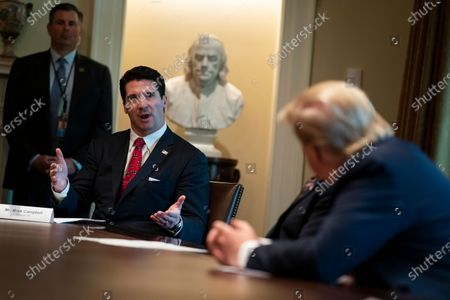 President Donald Trump listens as former NFL player Mark Campbell tells his story of recovery from COVID-19, in the Cabinet Room of the White House, in Washington