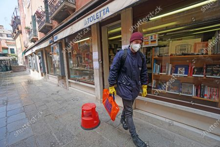 A young man leaves the historic La Toletta bookstore after making a purchase in Venice, Italy, 14 April 2020. From 14 April on, the new order of the Governor of Veneto Luca Zaia allows the partial reopening of the bookstores amid coronavirus lockdown.