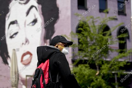 Person wearing a mask walks past the Elizabeth Taylor mural at the Dacha Beer Garden in the Shaw neighborhood, in Washington