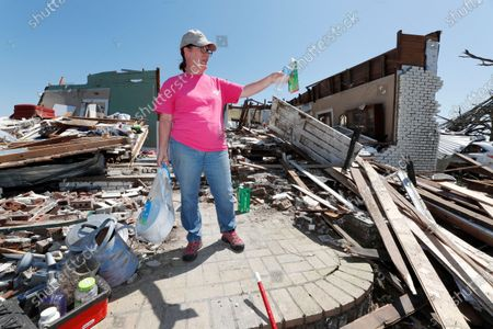 Julie Davis gestures as she speaks about her stepmother's house, now leveled from Sunday's tornado, in the Williamsburg community in rural Jefferson Davis County, Miss. The severe storm destroyed several neighborhoods and caused at least 12 fatalities statewide