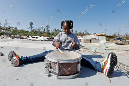 Ca'Loni Booth, 6, bangs away at what remains of the drum set in the slab that was James Hill Church in Prentiss, Miss., . The church and much of its south Prentiss neighborhood was heavily damaged by a tornado Sunday, one of several that swept the state, causing a number of deaths