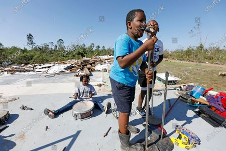 Kaden Poole, 10, foreground and his cousin Bralyn Washington, 9, sing a hymn while Ca'Loni Booth, 6, bangs away at what remains of the drum set on the slab that was James Hill Church in Prentiss, Miss., . The church and much of its south Prentiss neighborhood was heavily damaged by a tornado Sunday, one of several that swept the state, causing a number of deaths