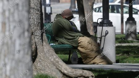Stock Picture of Man sits on a park bench, in Salt Lake City. Salt Lake City is leasing a hotel to shelter homeless people over 60 with underlying health conditions who are particularly vulnerable to coronavirus infections. People began checking into the 130-bed hotel Friday and can stay for at least two weeks with a possible extension, said county Mayor Jenny Wilson. Salt Lake City has confirmed a handful of cases in the homeless community, where preventative steps such as hand-washing and social distancing are more difficult