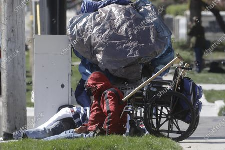 Stock Photo of Man sits near a sidewalk, in Salt Lake City. Salt Lake City is leasing a hotel to shelter homeless people over 60 with underlying health conditions who are particularly vulnerable to coronavirus infections. People began checking into the 130-bed hotel Friday and can stay for at least two weeks with a possible extension, said county Mayor Jenny Wilson. Salt Lake City has confirmed a handful of cases in the homeless community, where preventative steps such as hand-washing and social distancing are more difficult