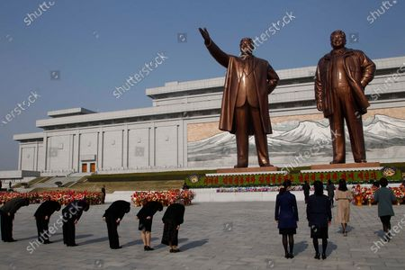 People bow in front of the bronze statues of late leaders Kim Il Sung and Kim Jong Il on the occasion of the 108th birth anniversary of Kim Il Sung in Pyongyang, North Korea