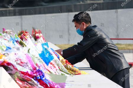 Man lays flowers in front of the bronze statues of late leaders Kim Il Sung and Kim Jong Il on the occasion of the 108th birth anniversary of Kim Il Sung in Pyongyang, North Korea