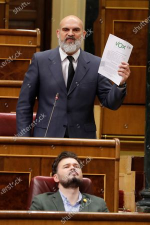 MP for the Spanish far-right party VOX, Victor Manuel Sanchez del Real (top), holds up a document while the parliamentary spokesman of the pro-Catalan independence party Republican Left of Catalonia (ERC), Gabriel Rufian (bottom), rolls his eyes during the first Prime Minister's questions session held since the declaration of the state of emergency, at the Congress of Deputies (lower house of the Spanish Parliament), in Madrid, Spain, 15 April 2020. The central government declared the state of emergency on 14 March and the Mediterranean country has since been under a strict lockdown in a bid to slow down the devastating spread of the pandemic COVID-19 disease caused by the SARS-CoV-2 coronavirus.
