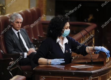 Stock Image of Cleaner Valentina Cepeda (R) disinfects the podium as right-wing Popular Party (PP) MP and member of the Board of Congress Adolfo Suarez Illana (L) looks on during the first Prime Minister's questions session held since the declaration of the state of emergency while an usher wearing a face mask (L) places a glass of water next to her stand, at the Congress of Deputies (lower house of the Spanish Parliament), in Madrid, Spain, 15 April 2020. The central government declared the state of emergency on 14 March and the Mediterranean country has since been under a strict lockdown in a bid to slow down the devastating spread of the pandemic COVID-19 disease caused by the SARS-CoV-2 coronavirus.