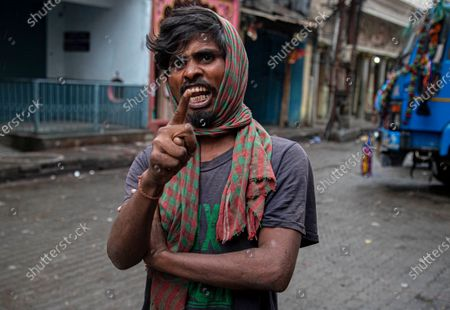 Ari Mandal, 27, an Indian migrant laborer gestures as he questions the authorities for not resuming train services to help people like him to return home during lockdown in Gauhati, India, . The new coronavirus causes mild or moderate symptoms for most people, but for some, especially older adults and people with existing health problems, it can cause more severe illness or death