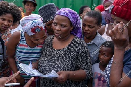 South African residents of Masiphumelele informal settlement look to see if they on a list of those vulnerable families earmarked to receive food parcels in the community of Masiphumelele, Cape Town, South Africa, 15 April 2020. The delivery of food was organized by the One South Africa Movement led by former Democratic Alliance leader (DA) Mmusi Maimane and the Living Hope Christian non-profit organization (NPO). Food collected from outlet Pick n Pay was delivered by volunteers who worked with local street captains that identified the most vulnerable in the community as beneficiaries. The South African government has extended a total lockdown of the country until the end of April to try stem the spread of the coronavirus SARS-CoV-2 which causes the Covid-19 disease.
