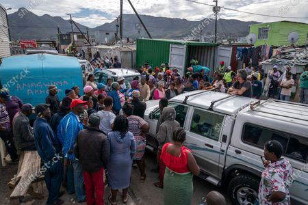 Stock Image of South African residents of Masiphumelele informal settlement gather around a vehicle as volunteers deliver food parcels to vulnerable families in the community of Masiphumelele, Cape Town, South Africa, 15 April 2020. The delivery of food was organized by the One South Africa Movement led by former Democratic Alliance leader (DA) Mmusi Maimane and the Living Hope Christian non-profit organization (NPO). Food collected from outlet Pick n Pay was delivered by volunteers who worked with local street captains that identified the most vulnerable in the community as beneficiaries. The South African government has extended a total lockdown of the country until the end of April to try stem the spread of the coronavirus SARS-CoV-2 which causes the Covid-19 disease.