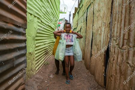 Stock Photo of South African girls carry food parcels to their shack  in the informal settlement of Masiphumelele, Cape Town, South Africa, 15 April 2020. The delivery of food was organized by the One South Africa Movement led by former Democratic Alliance leader (DA) Mmusi Maimane and the Living Hope Christian non-profit organization (NPO). Food collected from outlet Pick n Pay was delivered by volunteers who worked with local street captains that identified the most vulnerable in the community as beneficiaries. The South African government has extended a total lockdown of the country until the end of April to try stem the spread of the coronavirus SARS-CoV-2 which causes the Covid-19 disease.