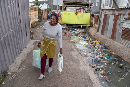 A South African woman carries food parcels to her shack in the informal settlement of Masiphumelele, Cape Town, South Africa, 15 April 2020. The delivery of food was organized by the One South Africa Movement led by former Democratic Alliance leader (DA) Mmusi Maimane and the Living Hope Christian non-profit organization (NPO). Food collected from outlet Pick n Pay was delivered by volunteers who worked with local street captains that identified the most vulnerable in the community as beneficiaries. The South African government has extended a total lockdown of the country until the end of April to try stem the spread of the coronavirus SARS-CoV-2 which causes the Covid-19 disease.