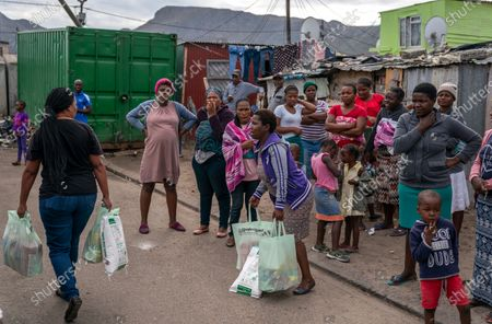 Stock Picture of Residents not on a list to receive food parcels look on as South African woman carry food parcels to their shack  in the informal settlement of Masiphumelele, Cape Town, South Africa, 15 April 2020. The delivery of food was organized by the One South Africa Movement led by former Democratic Alliance leader (DA) Mmusi Maimane and the Living Hope Christian non-profit organization (NPO). Food collected from outlet Pick n Pay was delivered by volunteers who worked with local street captains that identified the most vulnerable in the community as beneficiaries. The South African government has extended a total lockdown of the country until the end of April to try stem the spread of the coronavirus SARS-CoV-2 which causes the Covid-19 disease.