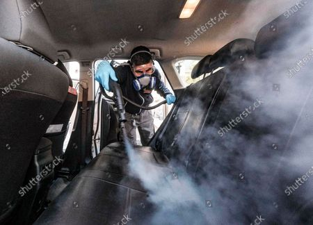 A taxi driver disinfects his car at a taxi cooperative in Milan, Italy, 15 April 2020, during the ongoing coronavirus COVID-19 pandemic. Italy is under lockdown in an attempt to stop the widespread of the Sars-Cov-2 coronavirus causing the COVID-19 disease.