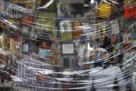 Siblings Julio Cesar, left, and Carmen Castellanos wear face masks as they wait for customers behind a protective sheet of plastic hanging over the counter in El Foquito, the hardware and electric supply store they own in the Benito Juarez district of Mexico City, . The Castellanos family used their hardware skills and supplies to hand-make more than 100 face shields which they donated to medical staff at two hospitals in the capital