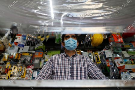 Julio Cesar Castellanos, 48, wears a face mask as he waits for customers behind a protective sheet of plastic hanging over the counter in El Foquito, the hardware and electric supply store he owns with his sister in the Benito Juarez district of Mexico City, . The Castellanos family used their hardware skills and supplies to hand-make more than 100 face shields which they donated to medical staff at two hospitals in the capital