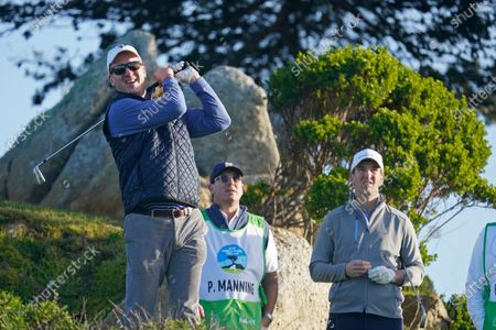 Peyton Manning, left, follows his shot from the 11th tee of the Monterey Peninsula Country Club Shore Course as his brother Eli Manning, right, stands nearby during the second round of the AT&T Pebble Beach National Pro-Am golf tournament in Pebble Beach, Calif. Peyton Manning plans to play a round of golf with an All In Challenge winner two guests, and then go to a restaurant for dinner with the winner and 10 guests. His recently retired brother, Eli, offered the Corvette he received as the MVP of the New York Giants' Super Bowl win over the Patriots in February 2012