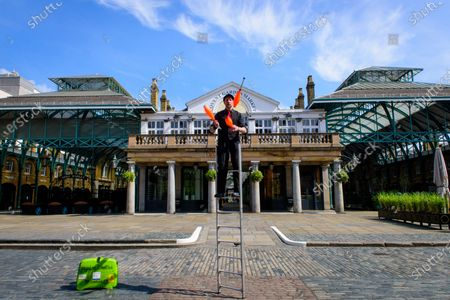 Stock Image of CoventNick, Nick Malinowski juggling on a ladder to make a promotional video for International Busking Day on 25 April, in an unusually empty Covent Garden, due to the Coronavirus lockdown.