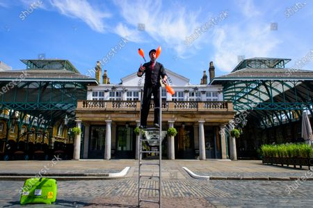 Stock Photo of CoventNick, Nick Malinowski juggling on a ladder to make a promotional video for International Busking Day on 25 April, in an unusually empty Covent Garden, due to the Coronavirus lockdown.