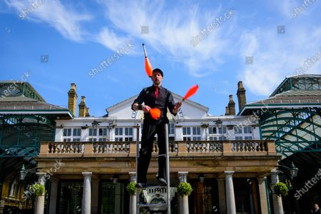 CoventNick, Nick Malinowski juggling on a ladder to make a promotional video for International Busking Day on 25 April, in an unusually empty Covent Garden, due to the Coronavirus lockdown.