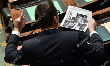 PVDA/PTB's Raoul Hedebouw pictured with an article on Flemish Minister President Jan Jambon during a plenary session of the chamber at the federal parliament, in Brussels, Thursday 16 April 2020.