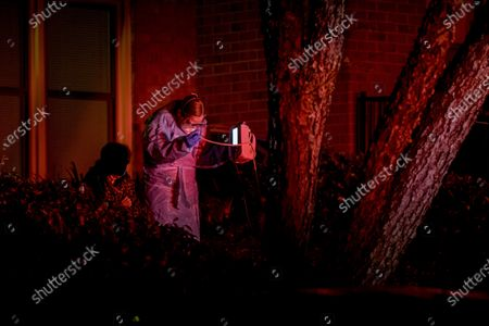 Bethesda-Chevy Chase Rescue Squad volunteer EMT Abby Smurzynski, right, strains to see her equipment in the dark as she responds to a call from a woman with coronavirus symptoms, left, in Potomac, Md., a suburb of Washington. After being checked out, the woman declined to be taken to the hospital and returned inside her home