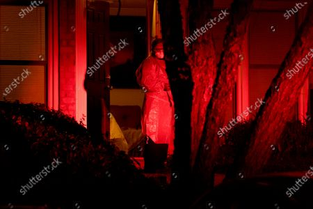 Stock Image of Bethesda-Chevy Chase Rescue Squad volunteer EMT Abby Smurzynski stands at the front door of a woman who called with coronavirus symptoms, in Potomac, Md., a suburb of Washington