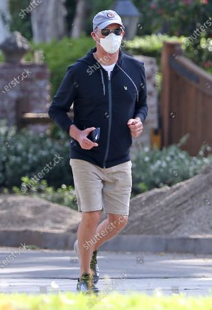Michael Keaton wears a face mask while going for a jog during the Coronavirus outbreak.