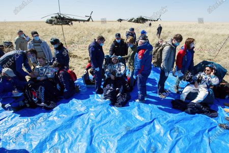 In this handout photo released by Gagarin Cosmonaut Training Centre (GCTC), Roscosmos space agency, U.S. astronauts Andrew Morgan, left, Jessica Meir, right, and Russian cosmonaut Oleg Skripochka sit in chairs shortly after the landing of the Russian Soyuz MS-15 space capsule near Kazakh town of Dzhezkazgan, Kazakhstan, . An International Space Station crew has landed safely after more than 200 days in space. The Soyuz capsule carrying NASA astronauts Andrew Morgan, Jessica Meir and Russian space agency Roscosmos' Oleg Skripochka touched down on Friday on the steppes of Kazakhstan. (Andrey Shelepin, Gagarin Cosmonaut Training Centre