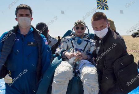 In this handout photo released by Gagarin Cosmonaut Training Centre (GCTC), Roscosmos space agency, rescue team members carry U.S. astronaut Andrew Morgan shortly after the landing of the Russian Soyuz MS-15 space capsule near Kazakh town of Dzhezkazgan, Kazakhstan, . An International Space Station crew has landed safely after more than 200 days in space. The Soyuz capsule carrying NASA astronauts Andrew Morgan, Jessica Meir and Russian space agency Roscosmos' Oleg Skripochka touched down on Friday on the steppes of Kazakhstan. (Andrey Shelepin, Gagarin Cosmonaut Training Centre