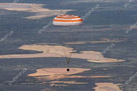 In this handout photo released by Gagarin Cosmonaut Training Centre (GCTC), Roscosmos space agency, the Soyuz MS-15 space capsule carrying International Space Station (ISS) crew members descends beneath a parachute just before landing in a remote area near Kazakh town of Dzhezkazgan, Kazakhstan, . An International Space Station crew has landed safely after more than 200 days in space. The Soyuz capsule carrying NASA astronauts Andrew Morgan, Jessica Meir and Russian space agency Roscosmos' Oleg Skripochka touched down on Friday on the steppes of Kazakhstan. (Andrey Shelepin, Gagarin Cosmonaut Training Centre