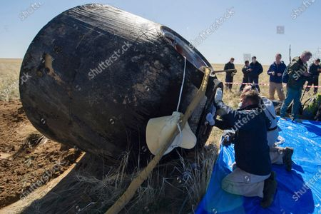 In this handout photo released by Gagarin Cosmonaut Training Centre (GCTC), Roscosmos space agency, rescue team members open the capsule hatch shortly after the landing of the Russian Soyuz MS-15 space capsule near Kazakh town of Dzhezkazgan, Kazakhstan, . An International Space Station crew has landed safely after more than 200 days in space. The Soyuz capsule carrying NASA astronauts Andrew Morgan, Jessica Meir and Russian space agency Roscosmos' Oleg Skripochka touched down on Friday on the steppes of Kazakhstan. (Andrey Shelepin, Gagarin Cosmonaut Training Centre