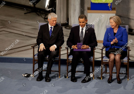 United States President Barack Obama looks at the Nobel Prize medal with Nobel Peace Prize Committee Chairman Thorbjorn Jagland and and Kaci Kullmann Five during the Nobel Peace Prize ceremony,  Raadhuset Main Hall at Oslo City Hall