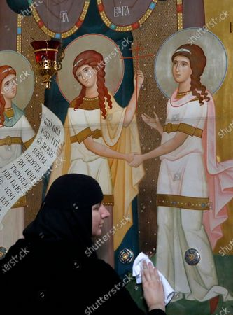 An Orthodox nun disinfects icons with antiseptic at the Saint-Elizabeth's monastery on the  Great Friday amid the ongoing pandemic of the COVID-19 disease caused by the SARS-CoV-2 coronavirus, as she prepares for the celebration of the Orthodox Easter at a nunnery on the outskirts of Minsk, Belarus, 17 April 2020. This year Orthodox Christians celebrate Easter on 19 April 2020.