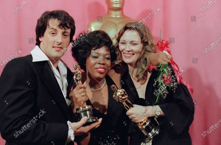 """Sylvester Stallone, left, holds his Oscar for his performance in """"Rocky,"""" Eletha Finch, center, holds the Oscar she accepted for her late husband, Peter Finch, who was named best actor for his performance in """"Network,"""" and Faye Dunaway holds the Oscar she won for best actress in """"Network,"""" at the Oscars in Los Angeles. """"Hoosiers"""" shot all the way to No. 1 in The Associated Press Top 25 of best sports movies, narrowly edging Academy Award Best Picture honoree """"Rocky"""" -- released in 1976"""