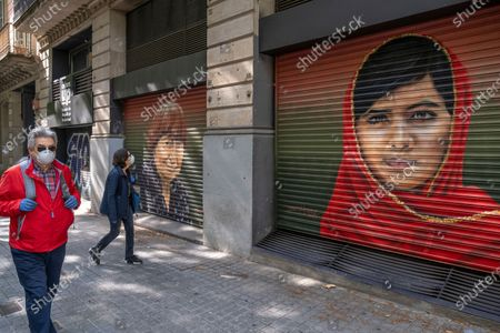 Stock Image of People walk past portraits of film director, Agnès Varda and Pakistani civil rights activist, Malala Yousafzai during confinement. Barcelona overcomes a month of home confinement and social distancing. It is already 34 days since March 15th when the Spanish Government decreed a state of emergency. Only essential services are functioning.