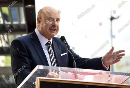"Stock Picture of Talk show host Dr. Phil McGraw speaking during a ceremony awarding him with a star on the Hollywood Walk of Fame in Los Angeles. Two television doctors - Dr. Oz and Dr. Phil - find themselves trying to explain comments made on Fox News Channel about the coronavirus. Dr. Mehmet Oz says he misspoke during an appearance where he said reopening schools was a ""very appetizing opportunity"" despite the coronavirus epidemic. Meanwhile, McGraw says he used bad examples while appearing on Laura Ingraham's show when he compared coronavirus deaths to deaths caused by cigarettes, auto accidents and swimming pools"