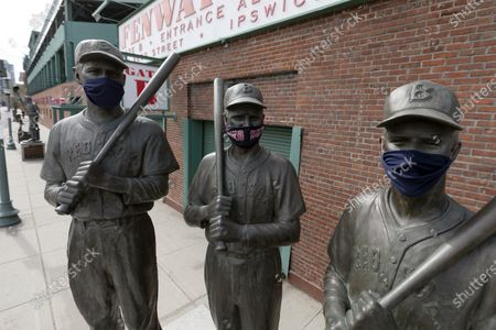 Statues of former Boston Red Sox greats, from left, Ted Williams, Bobby Doerr and Johnny Pesky, wear protective masks outside Fenway Park, in Boston