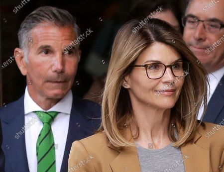 """Actress Lori Loughlin, front, and her husband, clothing designer Mossimo Giannulli, left, depart federal court in Boston. The judge overseeing the case against Loughlin, Giannulli and other parents charged with cheating the college admissions process called allegations of misconduct by investigators """"serious and disturbing"""