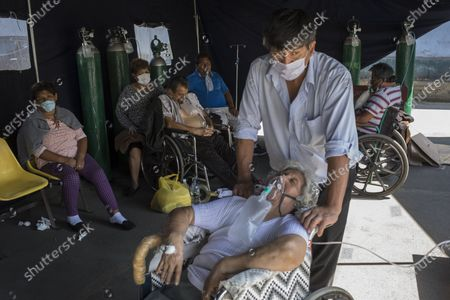 Stock Photo of Emma Salvador, 84, supplements her oxygen as her son Jose Gonzalez watches over her in a makeshift tent set up at the 2 de Mayo Hospital to treat people who are infected with the new coronavirus, in Lima, Peru