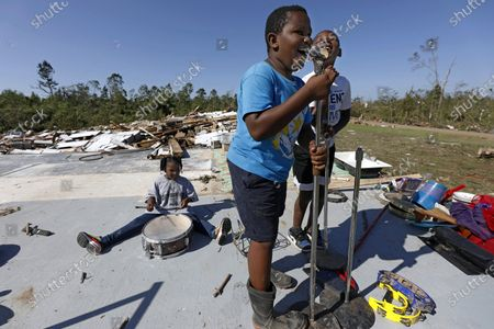 Stock Photo of Kaden Poole, 10, foreground and his cousin Bralyn Washington, 9, sing a hymn while Ca'Loni Booth, 6, plays on the remains of a drum set on the slab that was James Hill Church in Prentiss, Miss., . The church and much of its south Prentiss neighborhood was heavily damaged by a tornado Sunday, one of several that swept the state, causing fatalities
