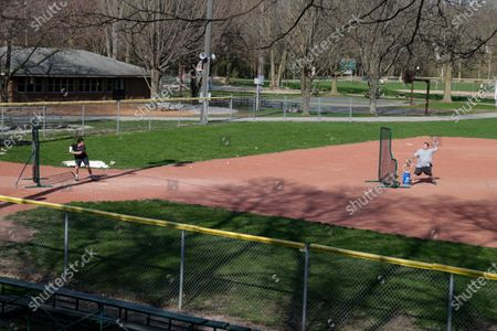 Wes Anderson throws to his son Case at Lions Park in Zionsville, Ind., as they practice in case baseball resumes after the season was stopped due to the coronavirus outbreak. Officials and experts are estimating tens of millions of dollars in losses for youth sports facilities because of the shutdown