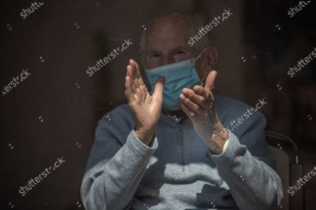 A resident of Alzheimer home wearing protective face mask claps his hands during performance of Czech popular singer Richard Krajco at courtyard near Prague in Pitkovice, Czech Republic, 18 April 2020.  Richard Krajco's short concert from mobile podium was a part of Pod okny (Under windows) project in which Czech singers sing under windows of retirement houses across Prague, Central and North Bohemia to help old people get in a better mood. The Czech government has imposed a lockdown in a bid to quell the spread of coronavirus.