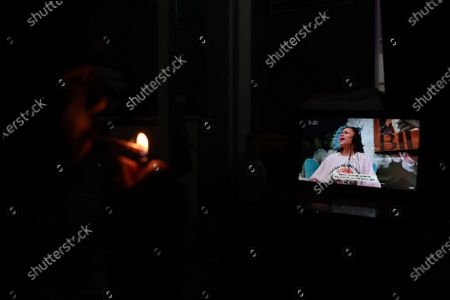 A man smokes a cigarette while watching Barbadian singer Rihanna performing during the 'One World: Together At Home' broadcast at his home in Paris, France, 18 April 2020. The eight-hour event run by the Global Citizen movement in cooperation with US artist Lady Gaga and the World Health Organization (WHO) is being live-streamed and broadcast on TV to support the health workers around the world fight with the SARS-CoV-2 coronavirus pandemic which causes the Covid-19 disease.
