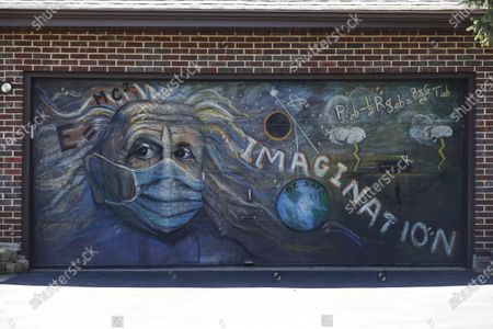 Garage door chalk mural of Albert Einstein wearing a mask by artist Kate Tully is displayed in Prospect Heights, Ill., . The Einstein mural came to Tully when she watched news coverage of the 50th anniversary of the historic Apollo 11 moon landing. Tully added the mask to her mural as people try to protect themselves from the coronavirus