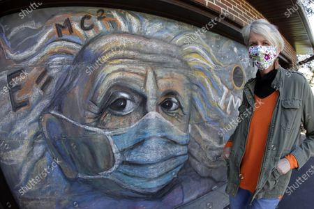 Artist Kate Tully stands in front of her garage door on which she chalked a mural of Albert Einstein wearing a mask in Prospect Heights Ill., . The mural came to Tully when she watched news coverage of the 50th anniversary of the historic Apollo 11 moon landing. She added the mask to Einstein as people try to protect themselves from the coronavirus pandemic