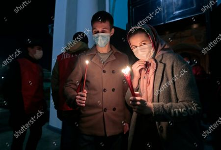 Members of the Russian Orthodox church hold candles during Easter Sunday celebrations in Moscow, 19 April 2020. Russian churches have celebrated Easter Sunday with services but with a limited number of believers due to coronavirus epidemic.
