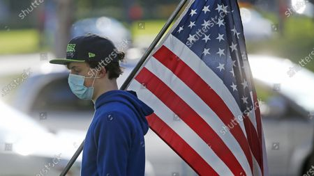 Stock Picture of Young man walks with a United States flag during the Utah Business Revival rally, in Salt Lake City. Utah will aim to reopen restaurants and gyms and resume elective surgeries in early May under a plan unveiled Friday, April 17, 2020, by Gov. Gary Herbert to gradually reopen the economy that has been decimated by the coronavirus pandemic